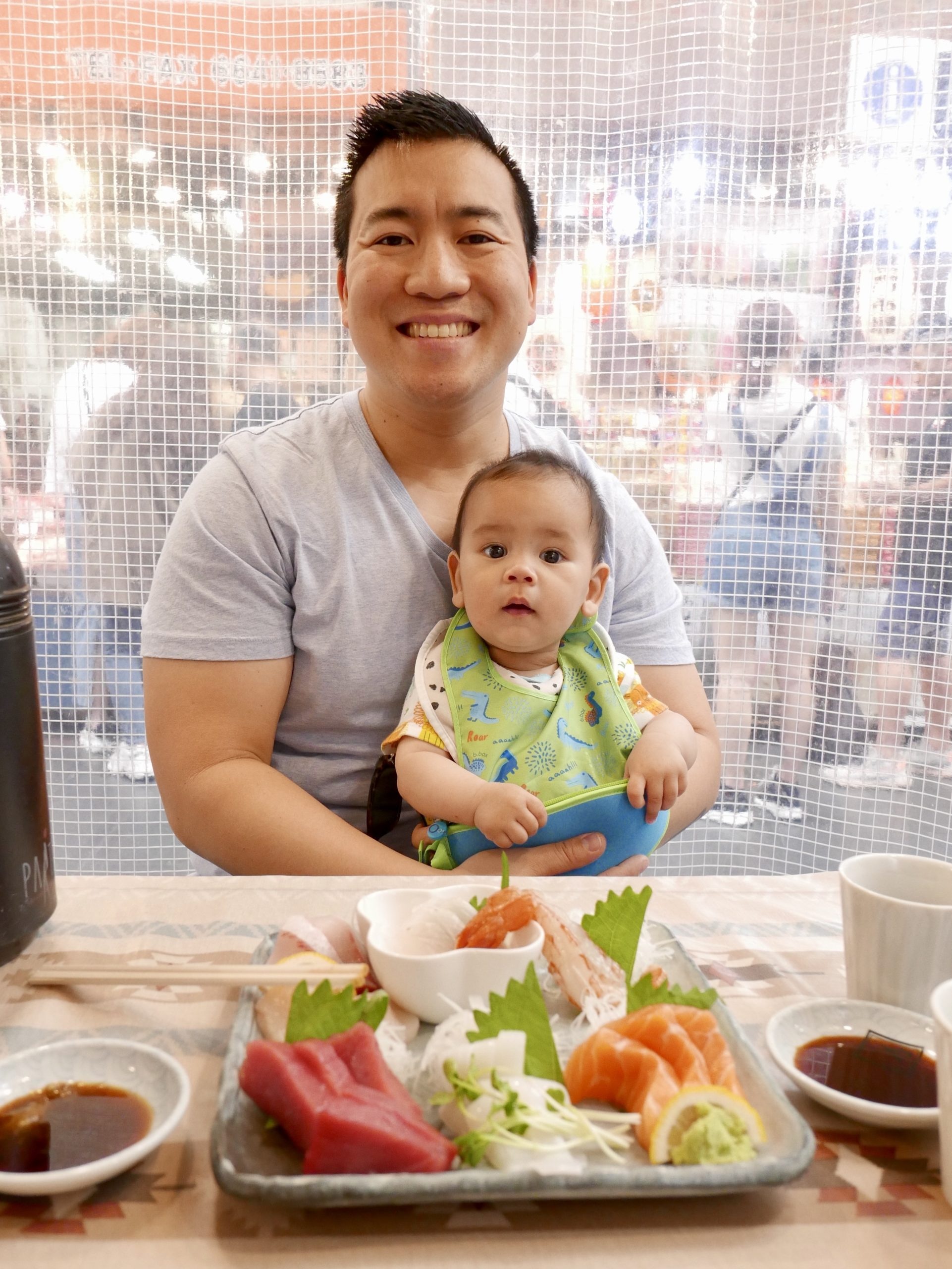 Dad holding baby in front of a table with a plate of sashimi