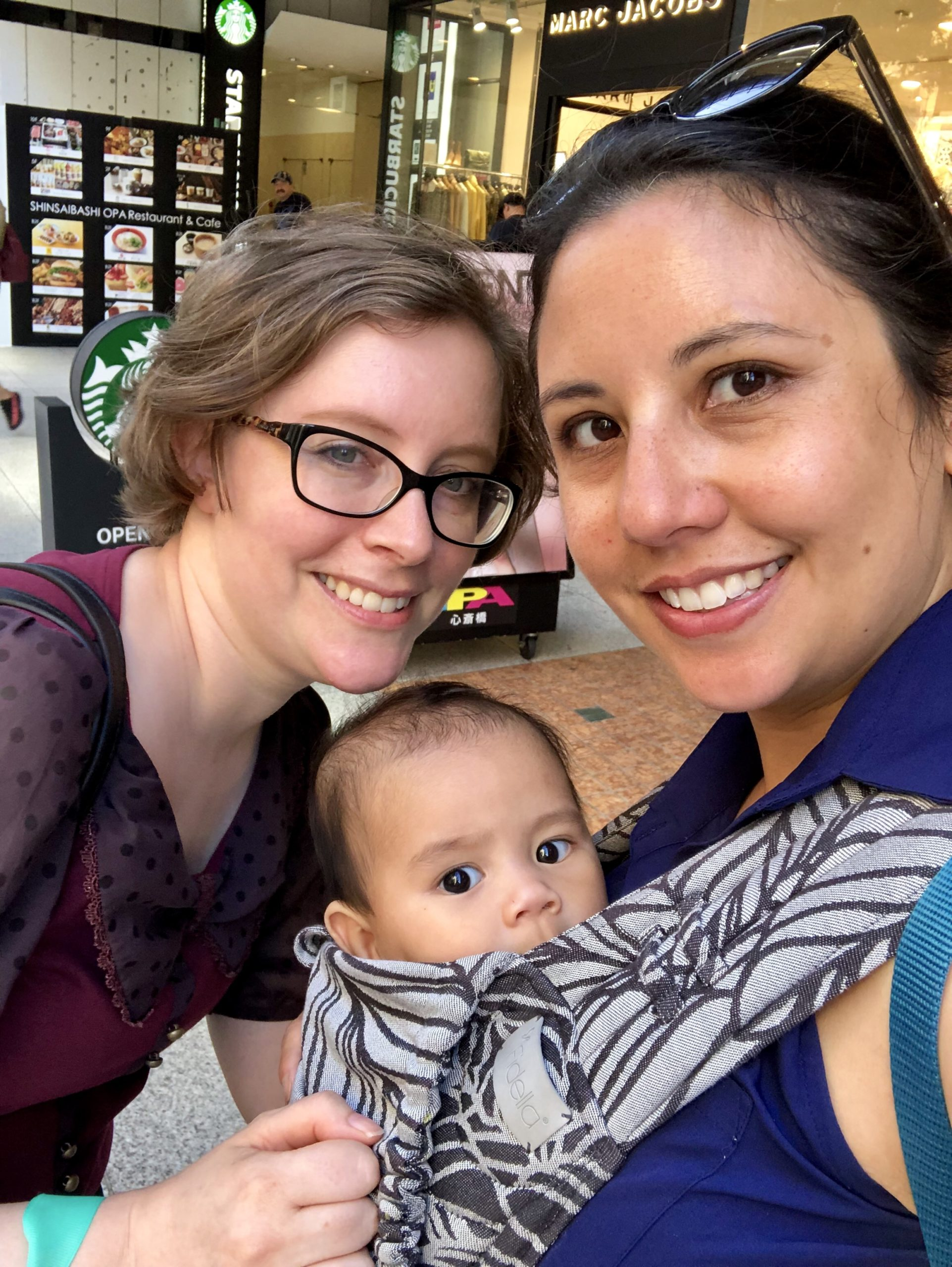 Two women, one holding a baby in a carrier