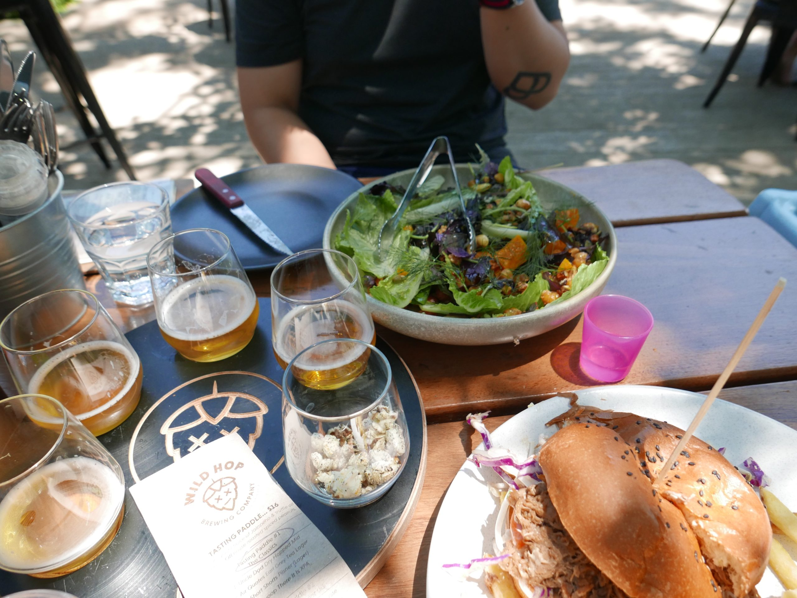 Beer tasting board, a large salad and a pulled pork burger