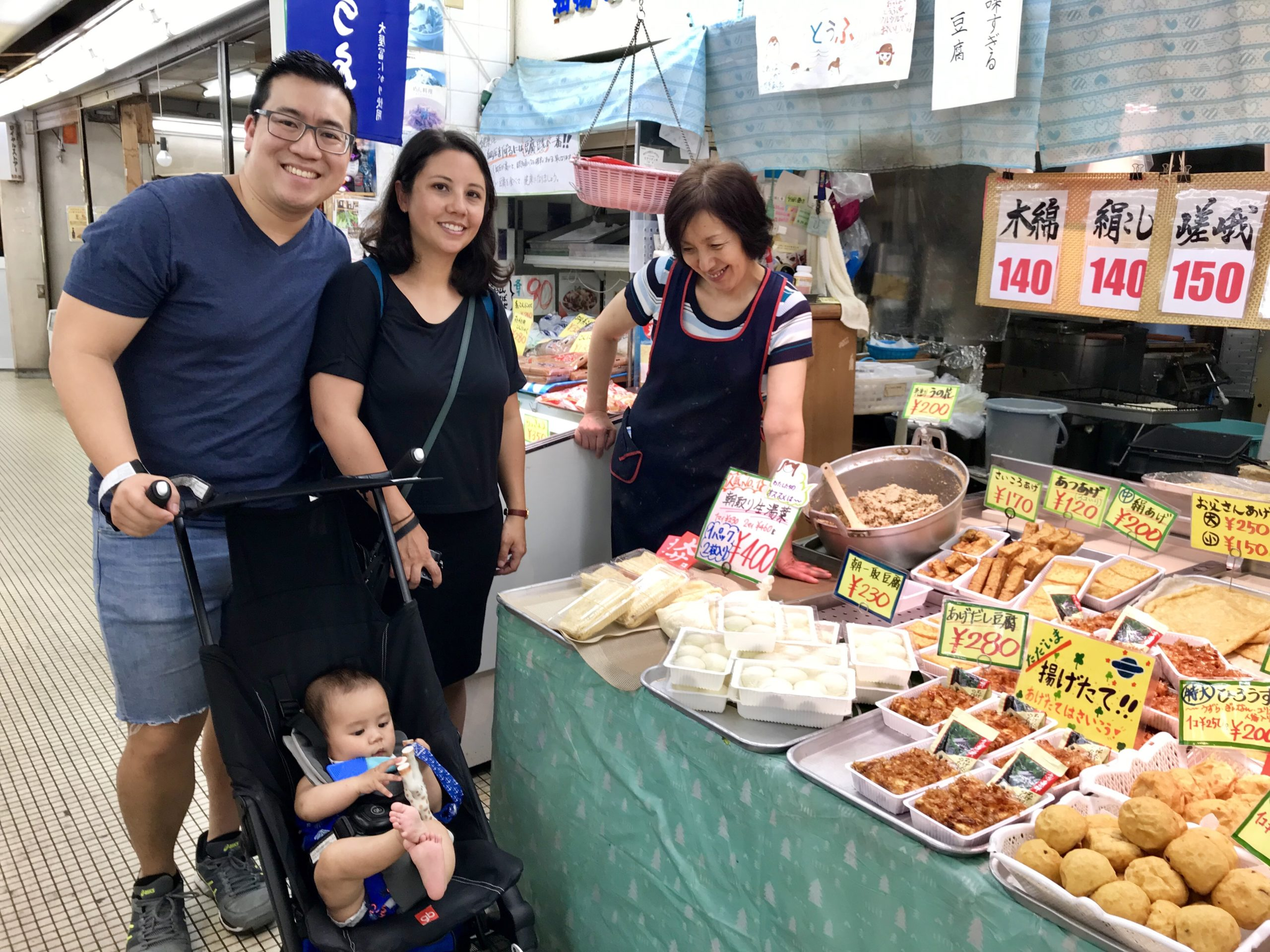 Mum, dad and baby in stroller with tofu seller at market
