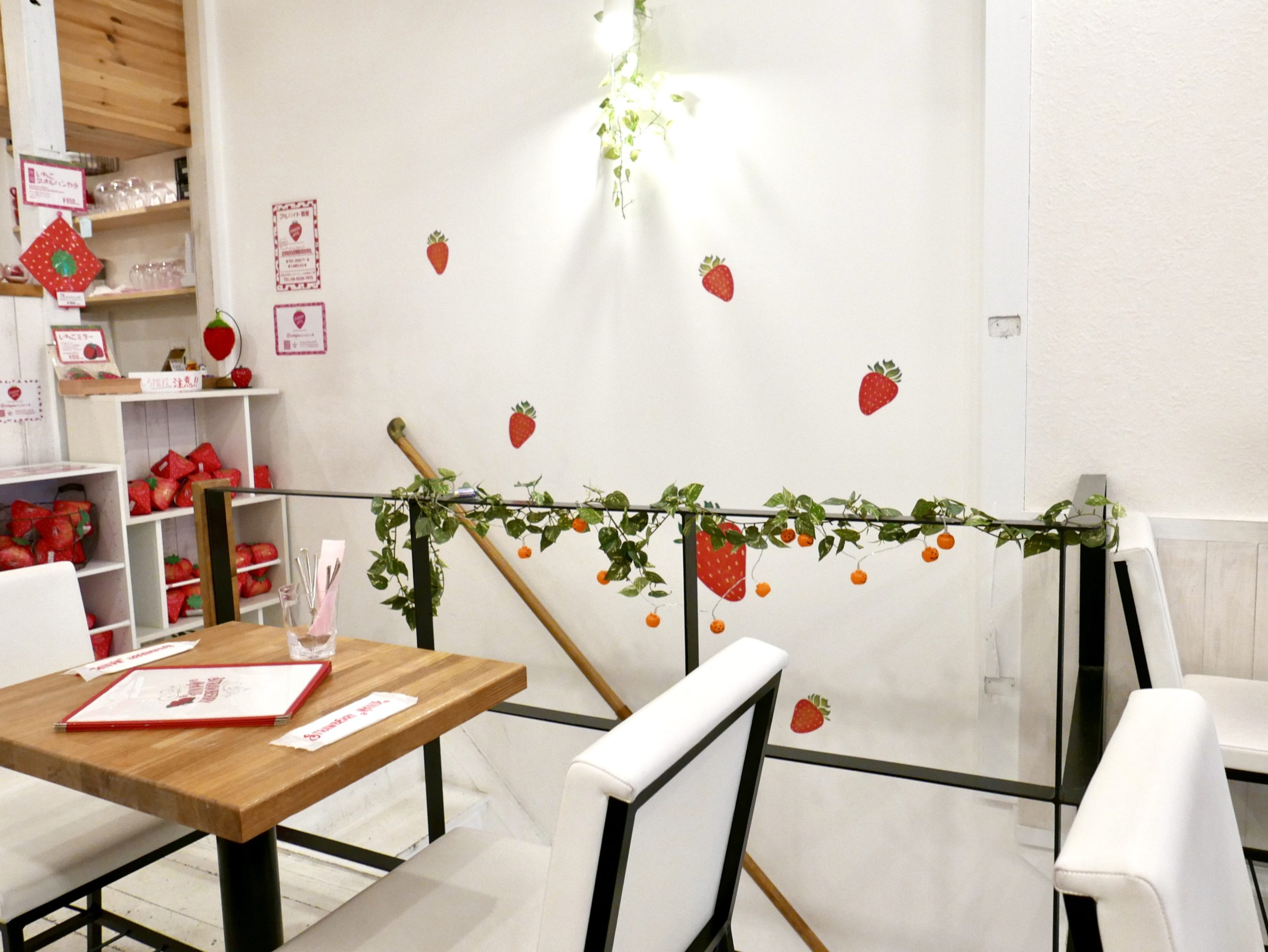 The inside of a cafe with strawberry themed decor