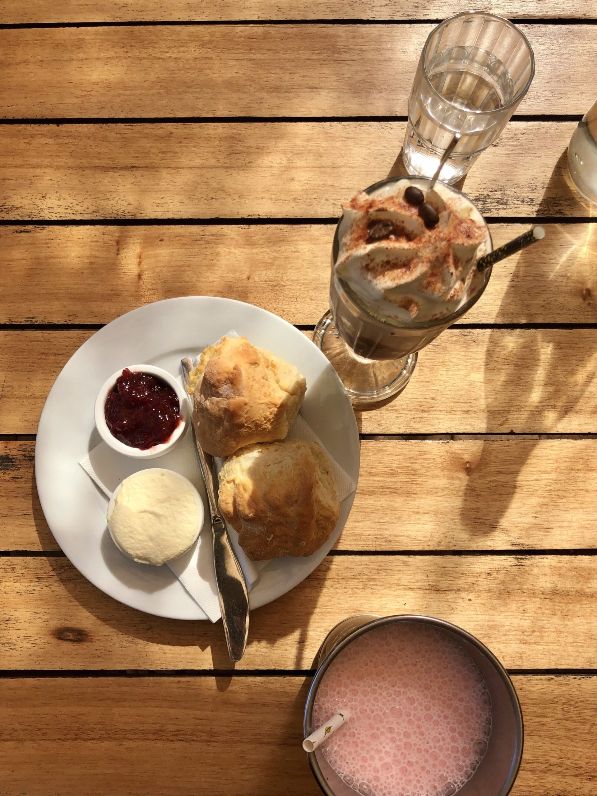 Plate with scones, cream and jam with a milkshake and an iced coffee