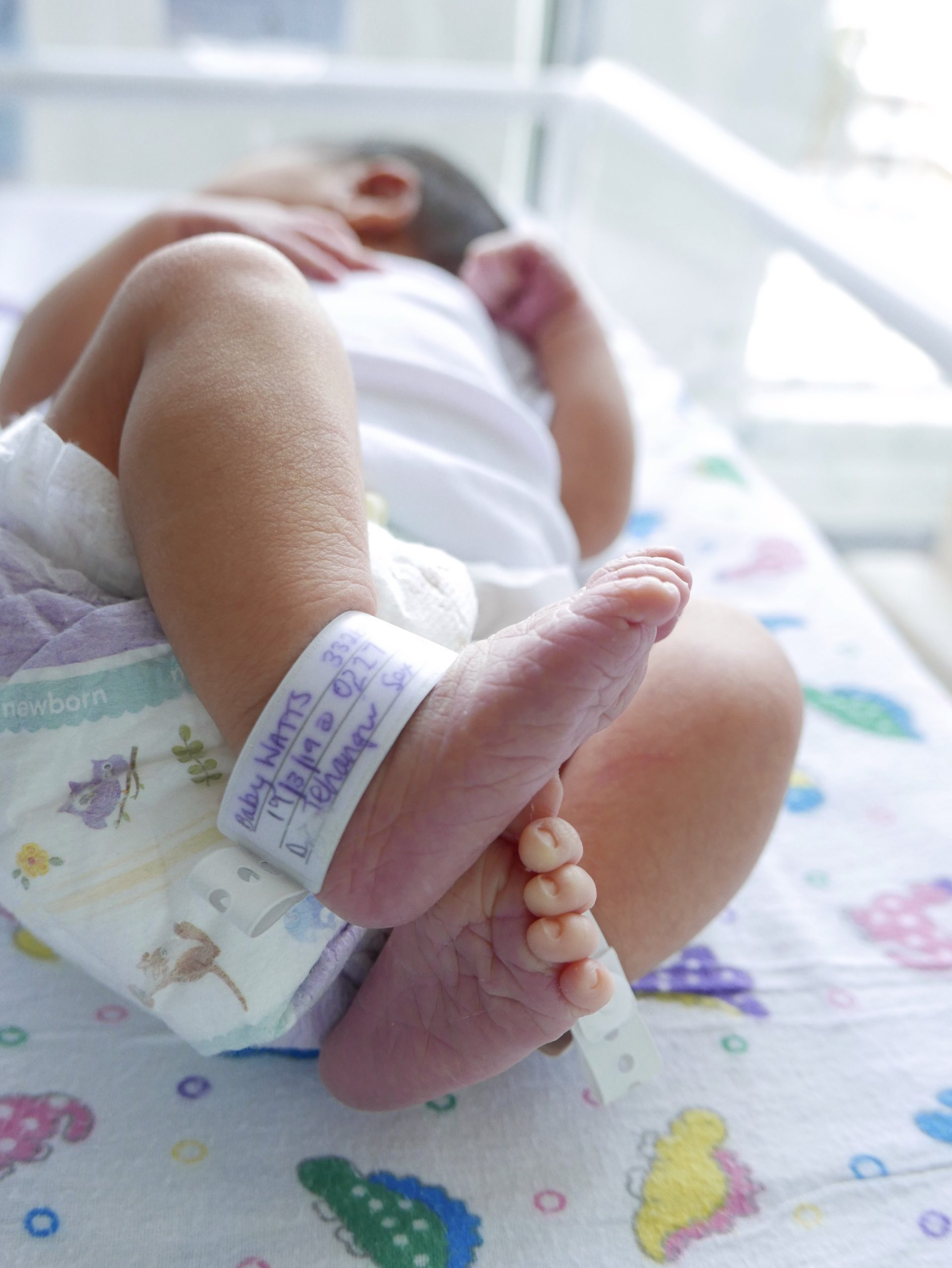 Closeup of newborn baby's feet with hospital anklet