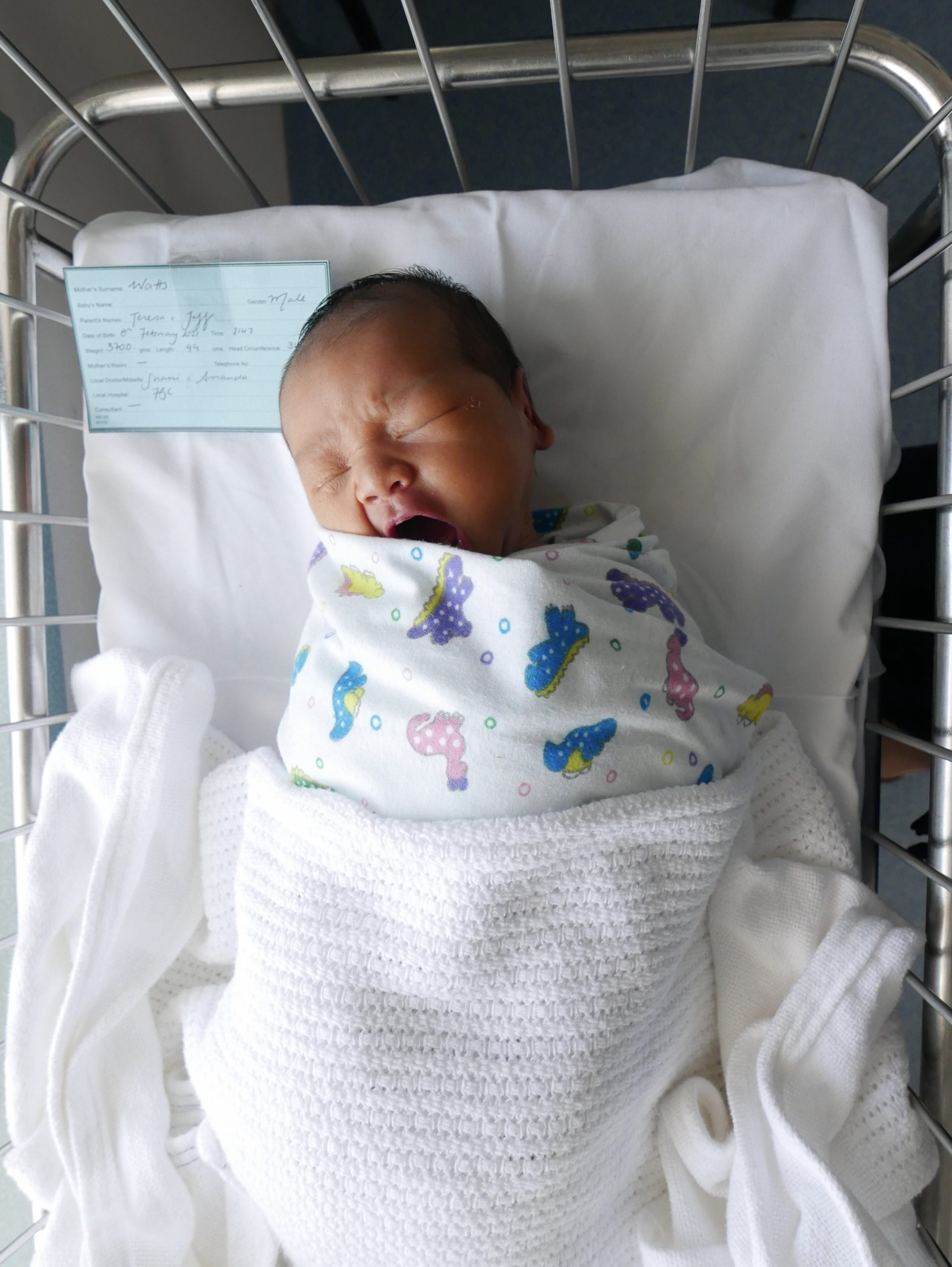 Yawning baby in a hospital bassinet