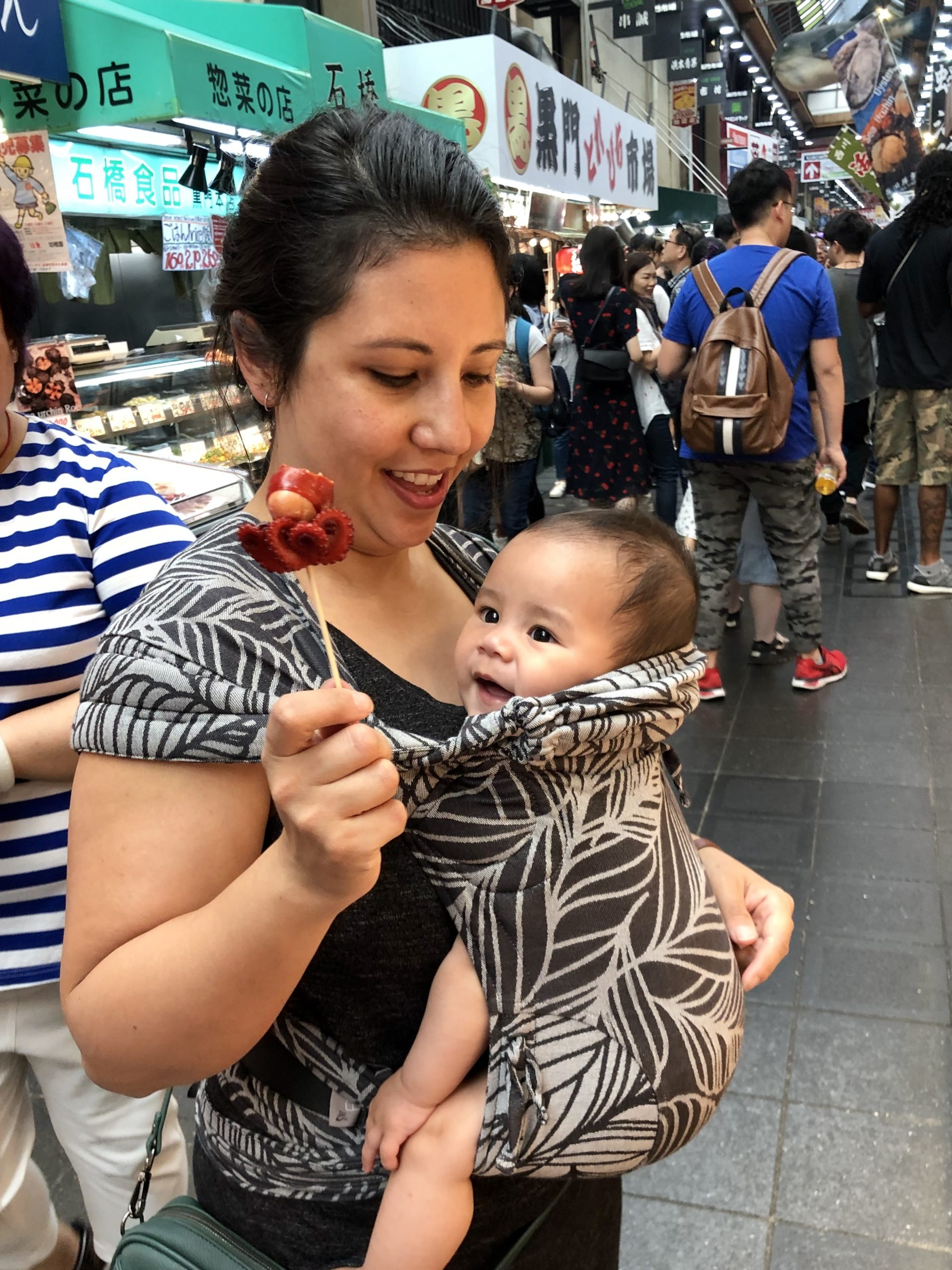 Mum with baby in carrier, holding a baby octopus on a stick