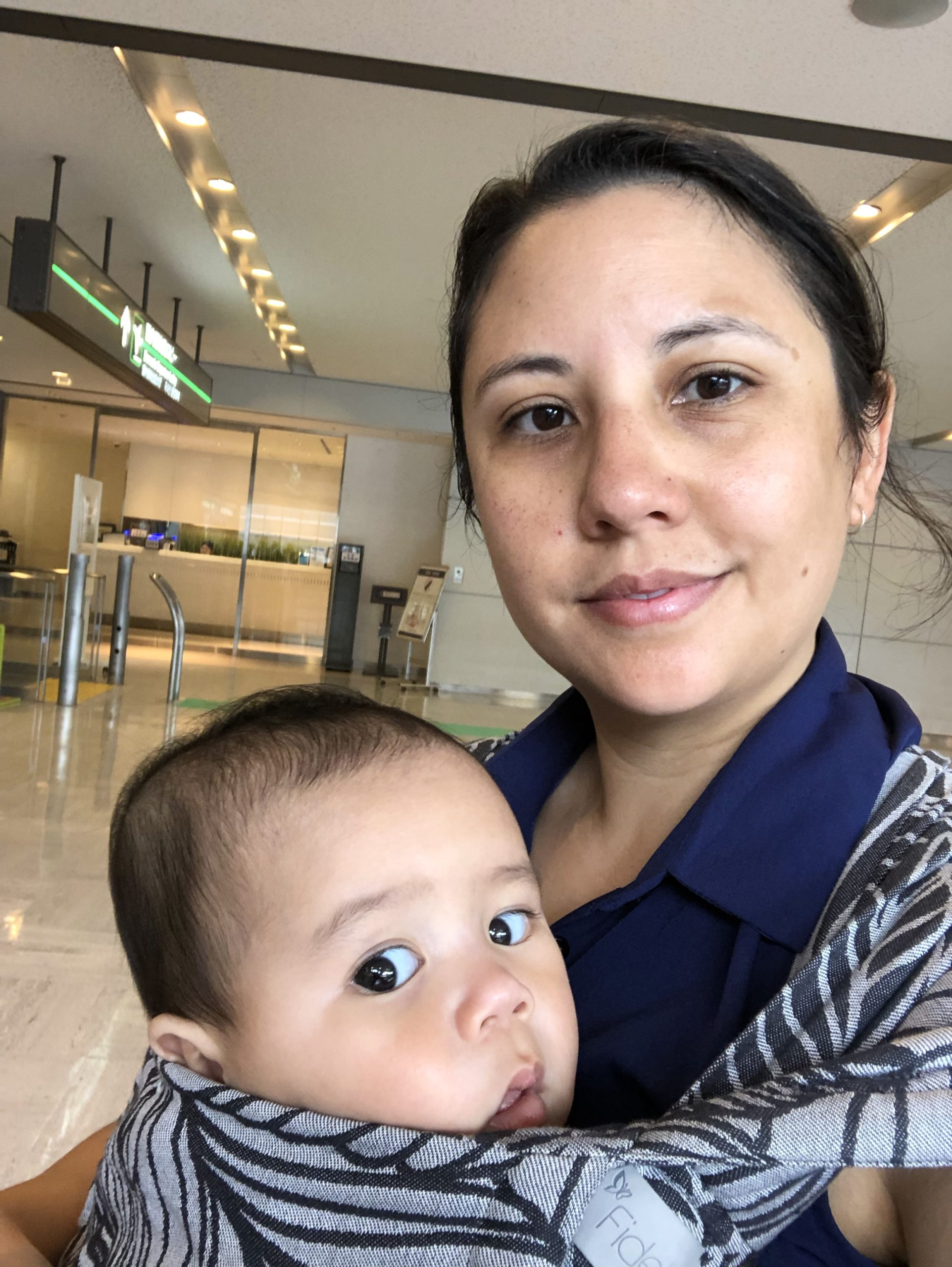 Tired mum with baby in carrier at airport