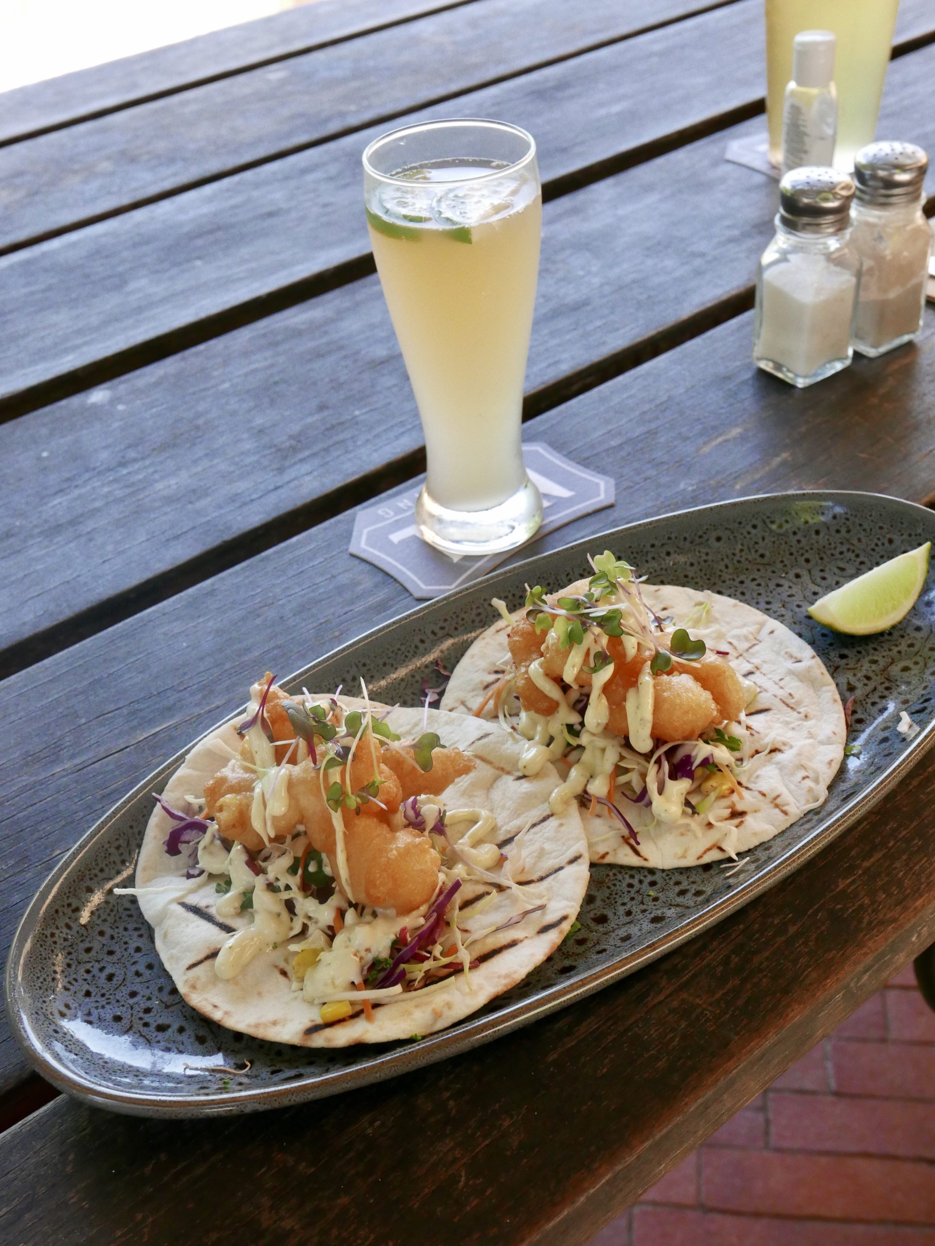 Two prawn tacos with beer in the background