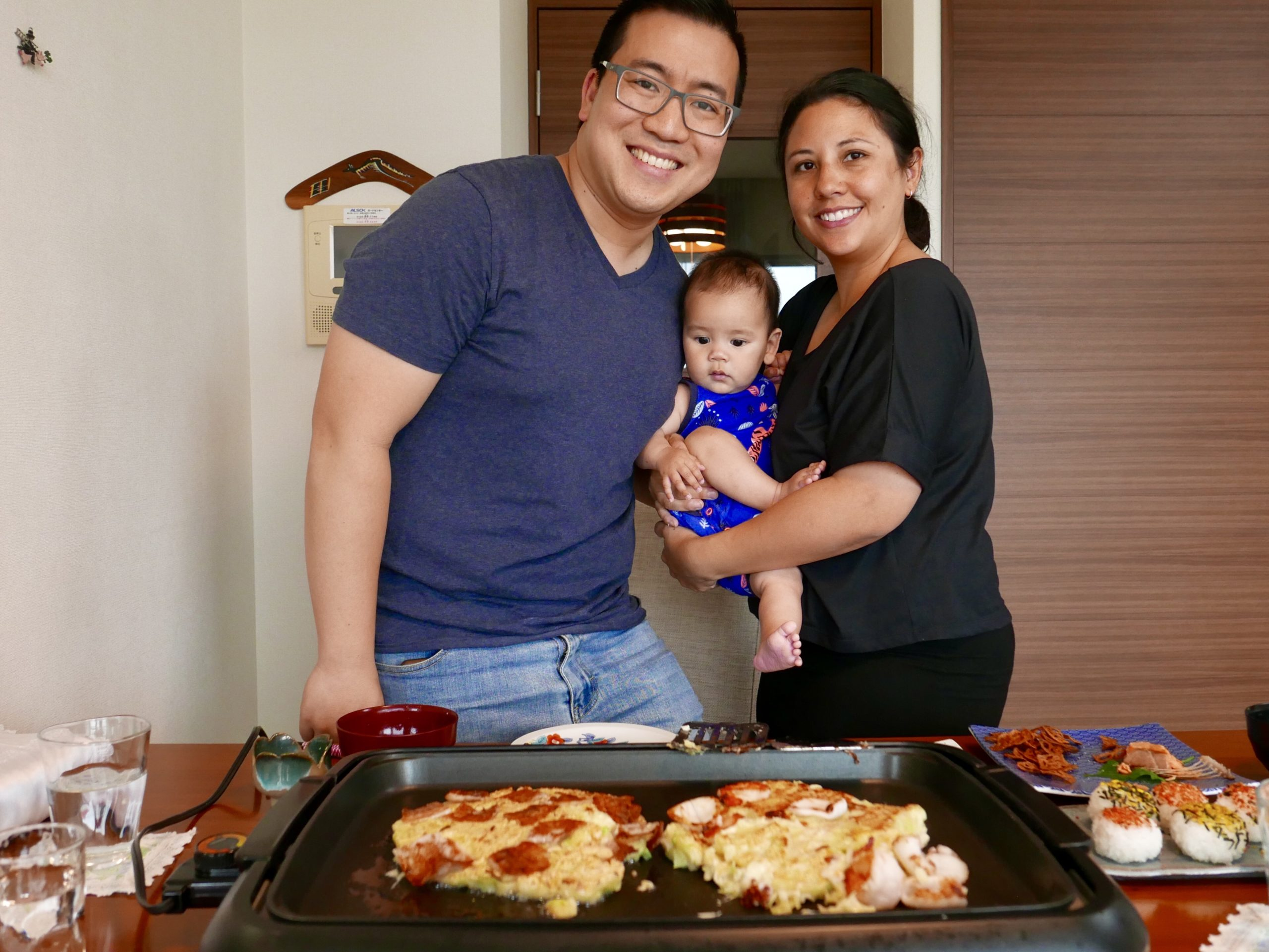 Mum, dad and baby in front of table of Japanese food